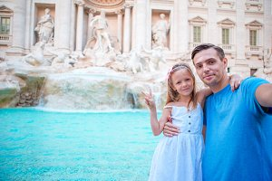 Young father and little girl making selfie background Trevi Fountain, Rome. Family portrait at famous places in Europe