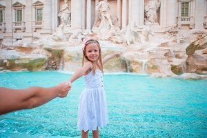 Adorable little girl at the Fountain of Trevi in Rome. Happy kid enjoy their european vacation in Italy