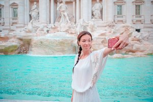 Beautiful girl taking selfie by the Fountain of Trevi in Rome. Happy woman enjoy her european vacation in Italy