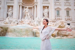 Happy woman enjoy view by the Fountain of Trevi during her trip in Rome, Italy