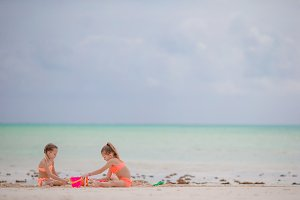 Adorable little girls playing with toys during beach vacation