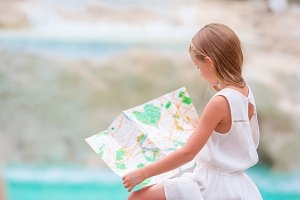 Adorable girl looking at touristic map near Trevi Fountain, Rome. Happy toodler kid enjoy italian vacation in Europe.