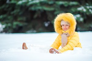 Little happy adorable girl in snow sunny winter day