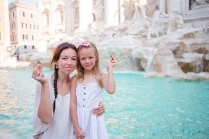 Mother and little girl trowing coin at Trevi Fountain, Rome for good luck. Little girl making a wish to come back.