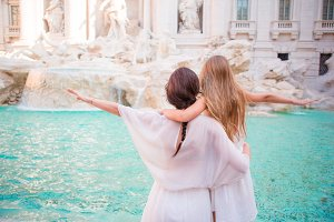 Mother and little girl at Trevi Fountain, Rome. Little girl making a wish to come back.