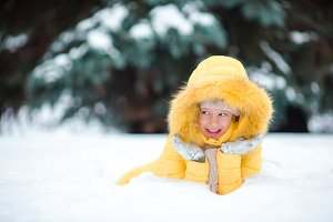 Portrait of little happy adorable girl in snow sunny winter day
