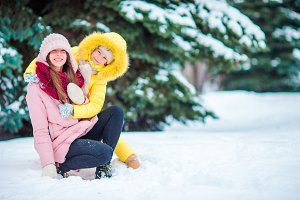 Happy mother and kid enjoy winter snowy day