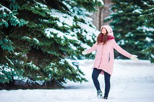 Happy girl enjoy winer and snow weather outdoors on beautiful cold day