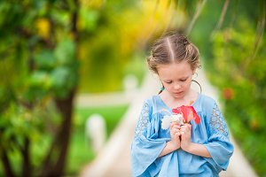 Adorable little girl with flower outdoors on summer vacation