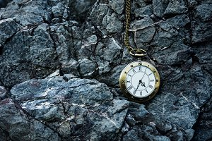 vintage golden pocket watch on rock