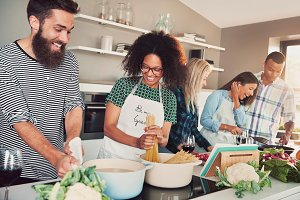 Group of friends cheerfully cooking