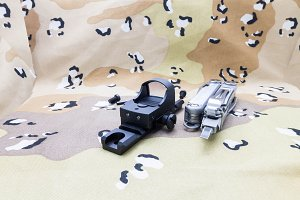 Reflex Sight on the sandy camouflage with a tool.