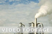 Factory smoke stack and pipes puff into air