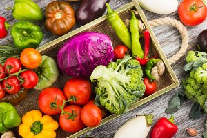 Set of different fresh raw colorful vegetables in the wooden tray