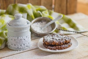 Cookies on the plate with sugar powder, sugar bowl and sugar strainer