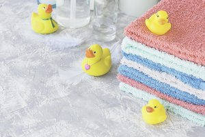 stack of towels with yellow rubber bath ducks on white marble background, space for text, selective focus