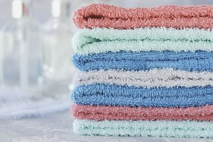 stack of towels for bathroom bottles on a white marble background, space for text, selective focus