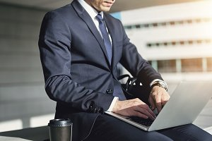 Man wearing suit typing on his notebook