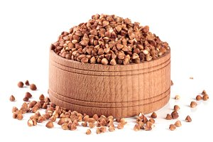 buckwheat in a wooden bowl isolated on white background