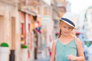 Adorable happy little girl outdoors in european city. Portrait of caucasian kid enjoy summer vacation in Europe