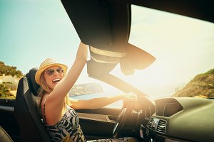 Laughing woman reaching above roof of car