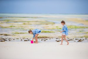 Adorable little girls playing with toys during low tide on Zanzibar