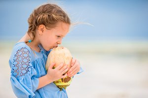 Little adorable girl drinking coconut milk on the beach
