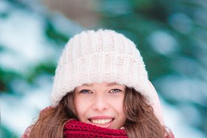 Portrait of beautiful girl smiling outdoors on beautiful winter snow day