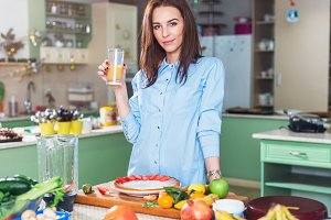 Pretty woman holding a glass of juice, smiling, looking at camera, standing  table with fresh fruit and vegetables on worktop