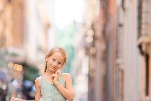 Adorable happy little girl outdoors in european city. Portrait of caucasian kid enjoy summer vacation in Rome