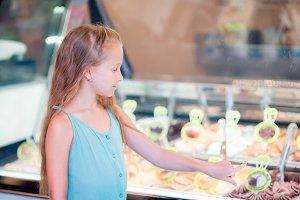 Adorable little girl eating ice-cream outdoors. Cute kid choose gelato in italian gelateria