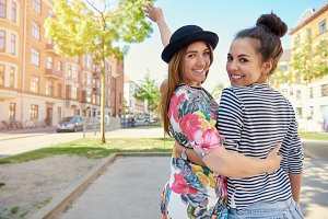 Happy friendly young women walking arm in arm