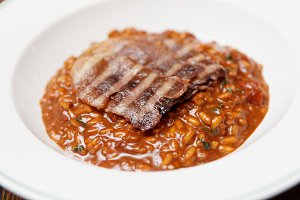 Rye risotto with grilled meat slices