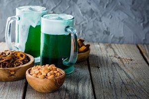 Green beer in mugs on rustic wood background
