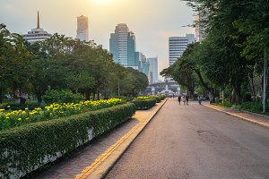 Business district cityscape from a Lumpini park with people walking at a sunset time in Bangkok, Thailand. Outdoor evening landscape with green park nature and skyscrapers on horizon at twilight, Asia