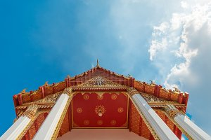 Traditional red roof with gold ornament of Chinese style temple bottom view with sunny blue sky in Bangkok,Thailand. Oriental buddhist architecture in Asia