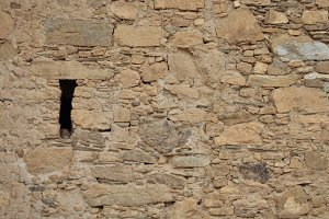Yellow stone wall with a hole