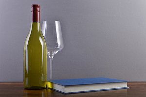 White wine with glass and book