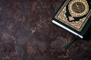 Islamic Book Koran on dark vintage background with arabic calligraphy that means the Holy Quran. Selective focus