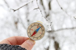 Traveler searching direction with a compass on background of winter forest