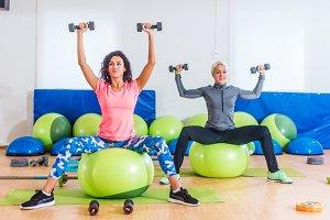 Sporty women training indoors doing exercise sitting on fitness balls lifting dumbbells