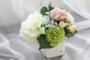 Colorful decoration artificial flower in enamel vase, horizontal, blur effect