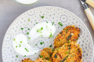 Vegetarian quinoa, carrot, coriander and green onion fritters served with yogurt on plate, vertical, top view