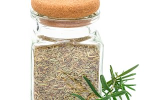 Dry rosemary tea in glass jar, isolated on white