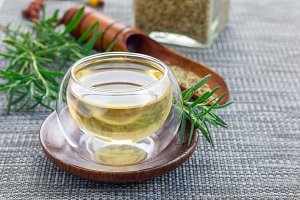 Herbal rosemary tea in a glass cup on oriental background, horizontal, copy space