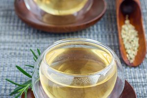 Herbal rosemary tea in a glass cup on oriental background, vertical