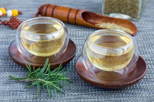 Herbal rosemary tea in a glass cup on oriental background, horizontal