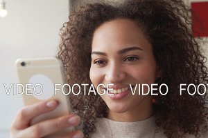 smiling african american young woman chatting using mobile phone