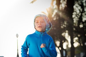 little boy running -with lens flare