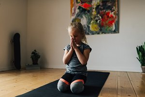 Little child exercising yoga at home